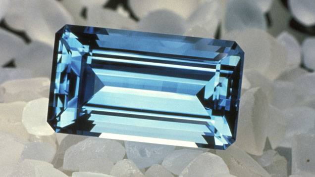 Single, faceted irradiated Topaz (blue), nested atop a series of rough Topaz.